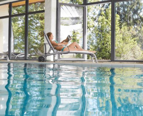 Unser Indoor-Schwimmbad mit großen Fenstern und Hotelgarten