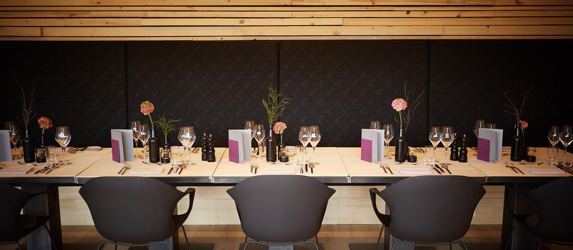 Tafel im Restaurant freistil. Gemütliche Stühle, schicke Bank, besondere Holzdecke