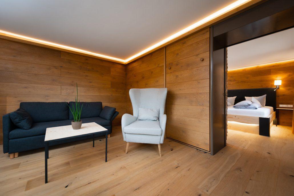 Holzwand mit gemütlicher Schlafcouch und Ohrensessel, unsere Suite. freistil. Boutiquehotel.