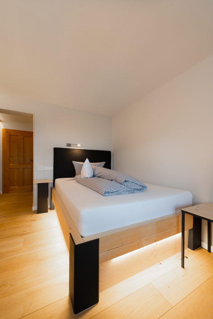 gemütliches Echtholzbett mit indirektem Licht. Einzelzimmer. freistil.